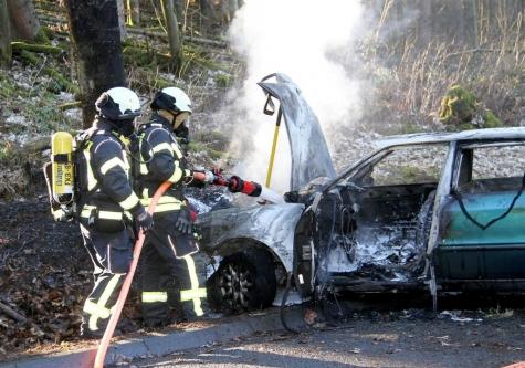 Feuerwehrmänner löschen brennenden Audi
